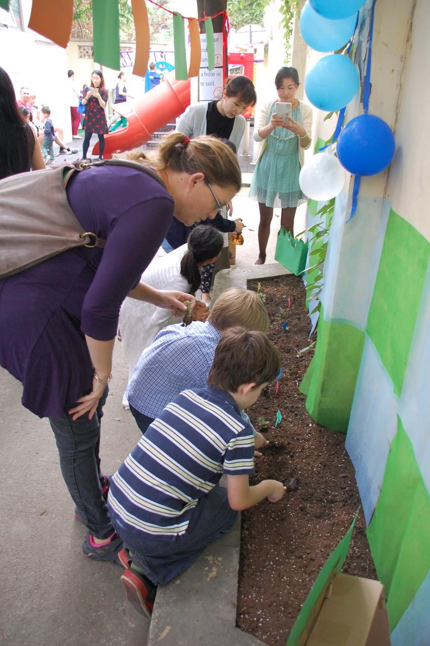 Kids planting seeds in the ELG Garden